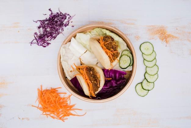 Une vue élevée de la cuisine traditionnelle de taiwan gua bao dans le paquebot avec salade sur fond de texture en bois Photo gratuit