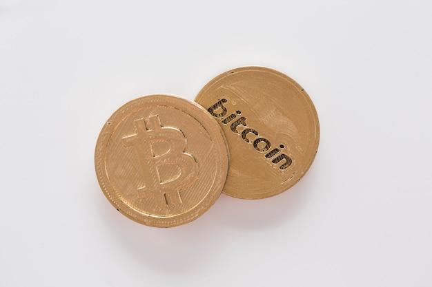 Vue élevée de deux bitcoins sur fond blanc Photo gratuit