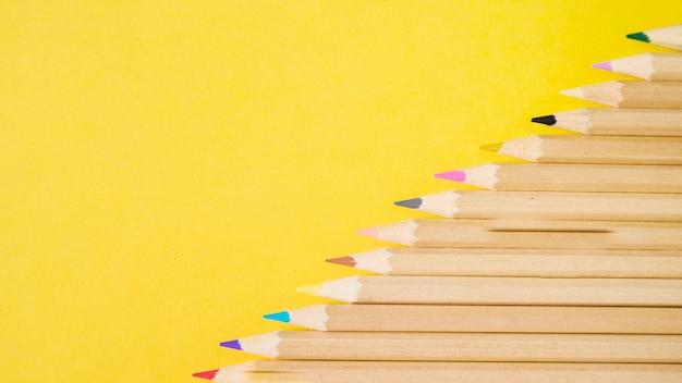 Vue élevée de divers crayons colorés sur fond jaune Photo gratuit