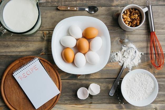 Vue élevée de divers ingrédients avec le bloc-notes en spirale montrant le mot de recette Photo gratuit