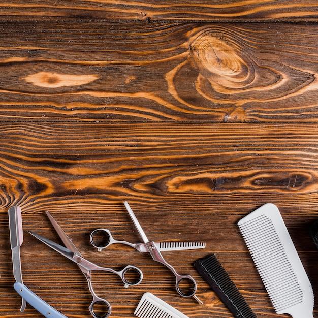 Vue élevée de divers outils de coiffeur sur fond en bois Photo gratuit