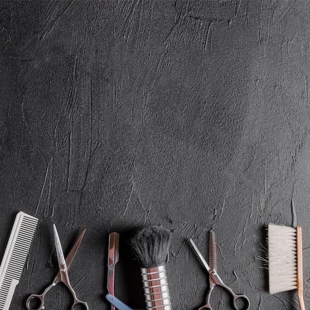 Vue élevée de divers outils de coiffeur sur fond noir Photo gratuit