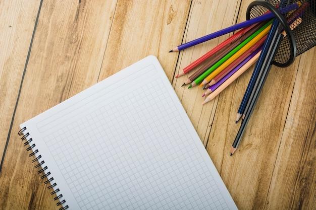 Vue élevée du bloc-notes et des crayons colorés sur fond en bois Photo gratuit