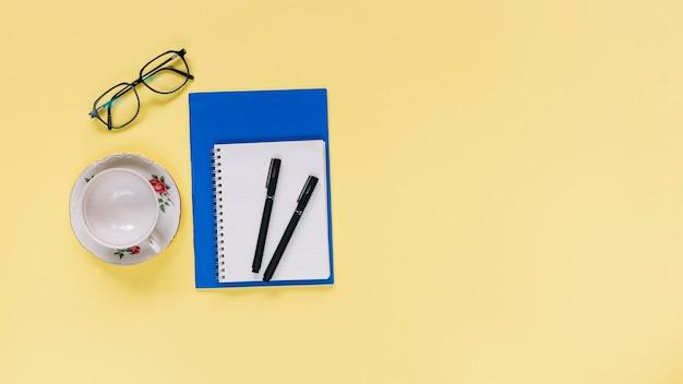 Vue élevée du bloc-notes en spirale; tasse et lunettes sur fond jaune Photo gratuit