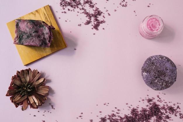 Une vue élevée du pain de savon; fleurs séchées et gommage corporel sur fond rose Photo gratuit