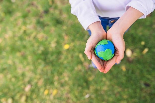 Vue élevée du petit globe d'argile dans les mains en coupe au-dessus de l'herbe Photo gratuit