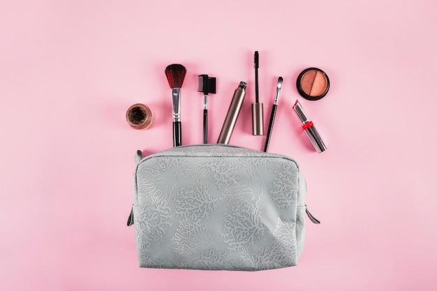 Vue élevée du sac cosmétique contenant du rouge à lèvres; mascara; eye-liner et brosses sur fond rose Photo gratuit