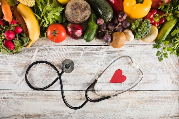 Vue élevée du stéthoscope en forme de cœur près de légumes frais sur un bureau en bois Photo gratuit