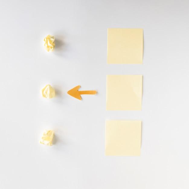 Vue élevée Du Symbole De La Flèche Entre Les Papiers Froissés Et Les Notes Adhésives Photo gratuit