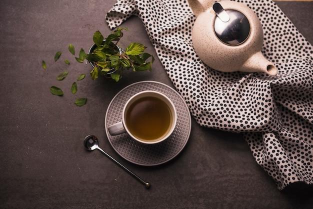 Vue élevée du thé; feuilles; théière et textile à pois sur table Photo gratuit