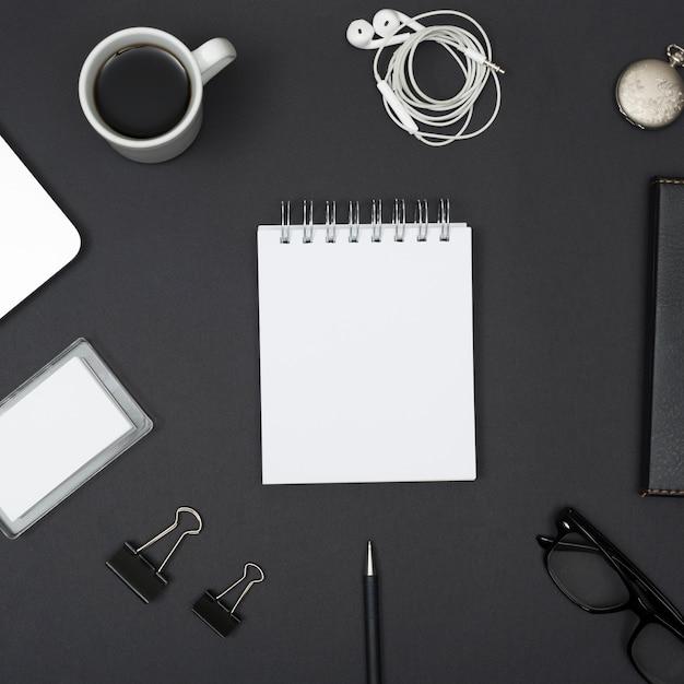 Vue élevée de l'écouteur; tasse à café; trombones; monocle; avec bloc-notes blanc vierge disposée sur fond noir Photo gratuit