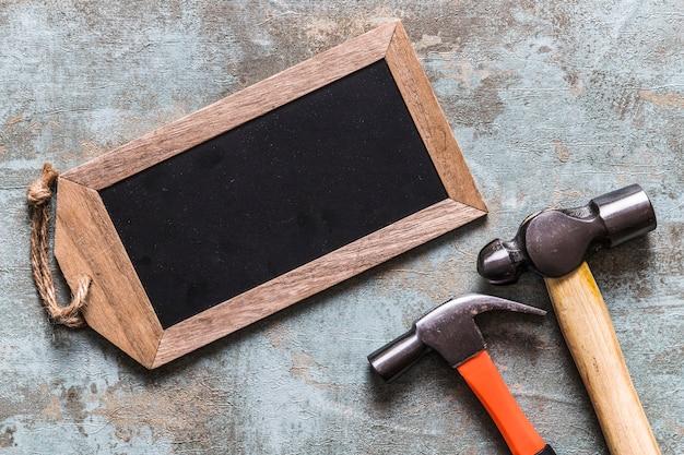 Vue élevée de l'étiquette en bois vierge et deux marteaux Photo gratuit