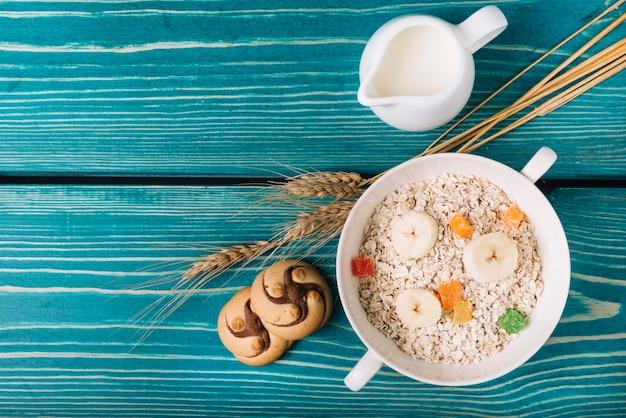 Vue élevée de farine d'avoine avec du lait et des biscuits sur la table Photo gratuit