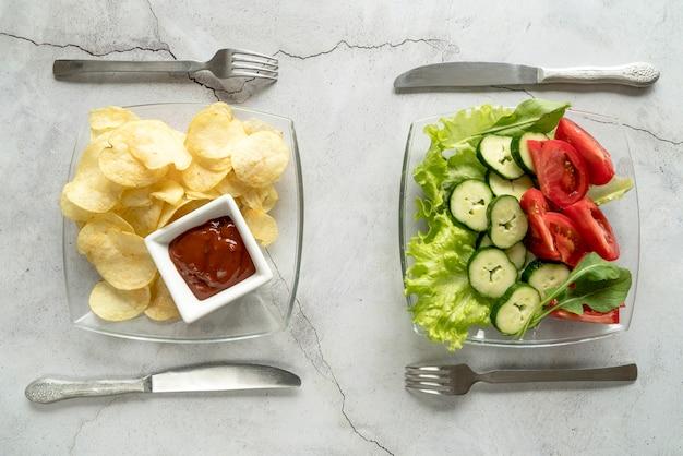 Vue élevée, frites, chips, pomme terre, et, salade végétarienne, à, couteau, et, fourchette Photo gratuit