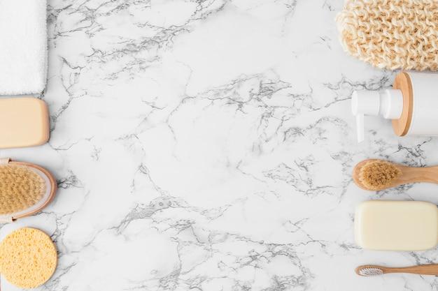 Vue élevée de gant de gommage; éponge; serviette; bouteille cosmétique; pinceau et savon sur fond de marbre Photo gratuit