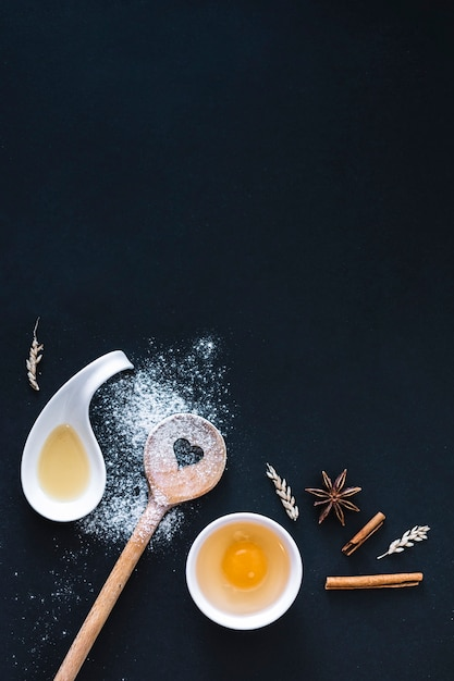 Vue élevée d'ingrédients de cuisson sur une surface noire Photo gratuit