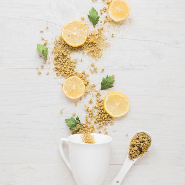 Vue élevée d'ingrédients de thé au citron avec une tasse en céramique et une cuillère Photo gratuit