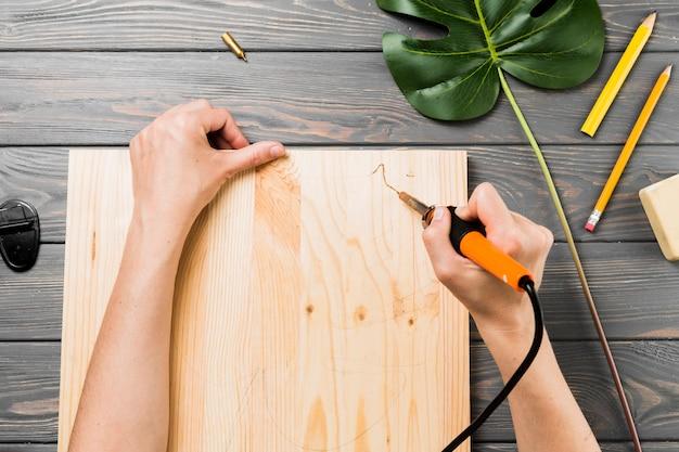 Vue élevée, main, découper, dur, planche en bois, sur, bureau Photo gratuit