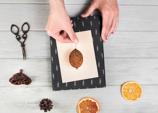 Vue élevée de la main faisant la carte de voeux avec feuille séchée; pomme de pin; tranche d'agrume et gousse de lotus sur la table Photo gratuit