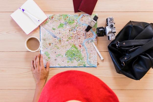 Vue élevée, de, main femme, à, accessoires voyageur, et, tasse thé, sur, bureau Photo gratuit