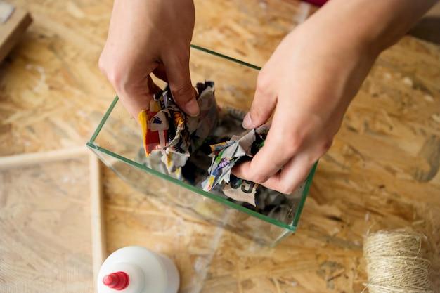 Vue élevée de la main d'une femme mettant du papier déchiré dans un récipient en verre Photo gratuit