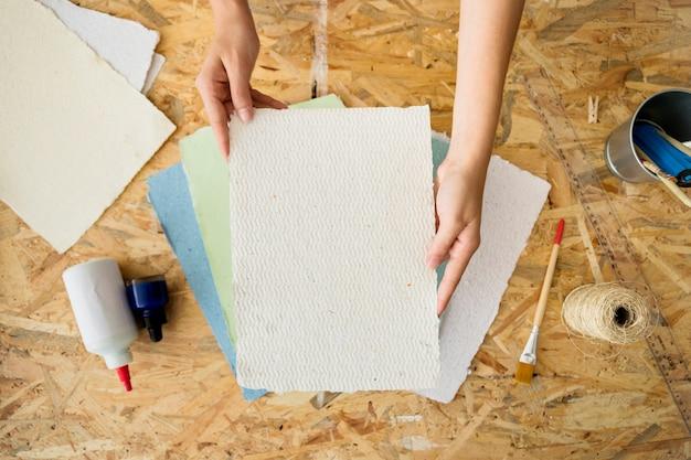 Vue élevée de la main d'une femme tenant un papier fait à la main Photo gratuit