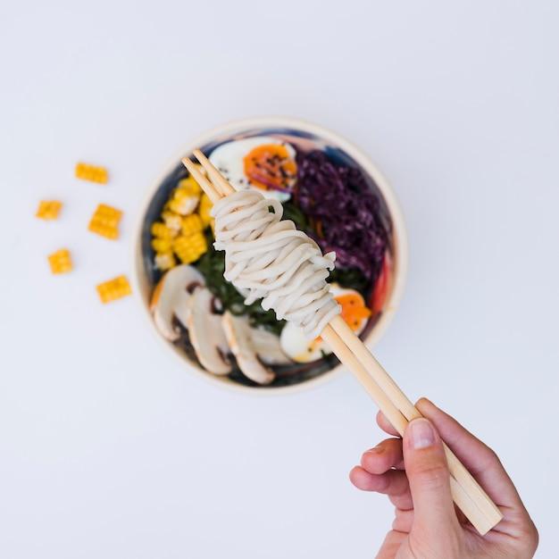Une vue élevée de la main d'une personne tenant des nouilles sur des baguettes sur la cuisine asiatique Photo gratuit