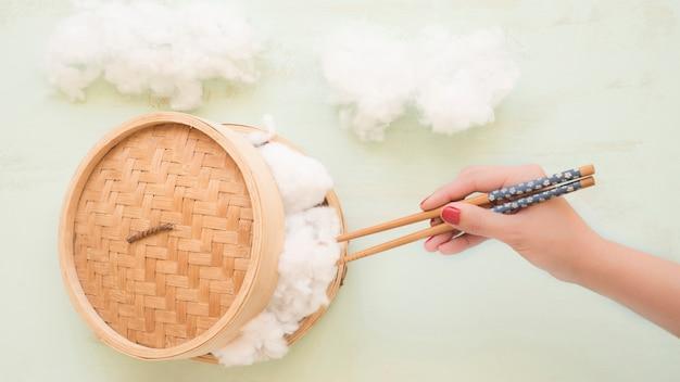 Vue élevée D'une Main Tenant Le Coton Avec Des Baguettes De Steamer En Osier Photo gratuit
