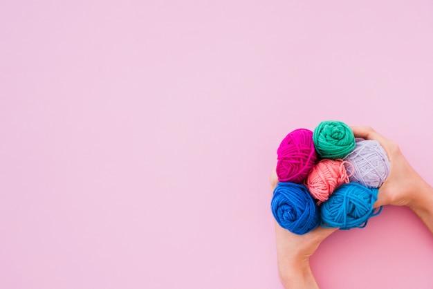 Une vue élevée de la main tenant une laine colorée sur fond rose Photo gratuit