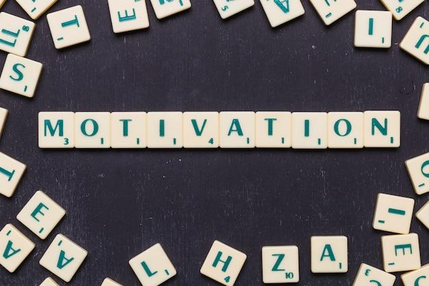 Vue élevée de mot de motivation faite à partir de lettres scrabble jeu Photo gratuit