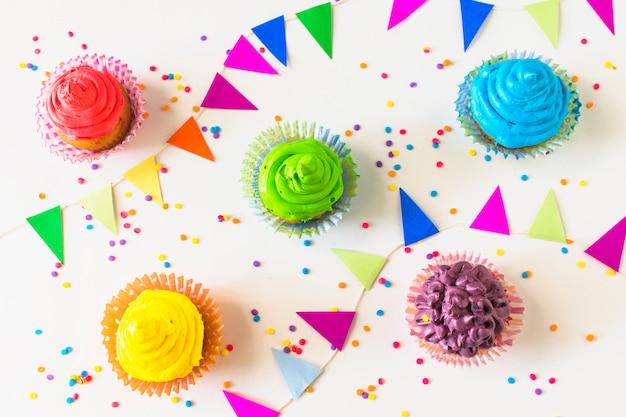 Vue élevée de muffins colorés; bruant et confettis sur une surface blanche Photo gratuit