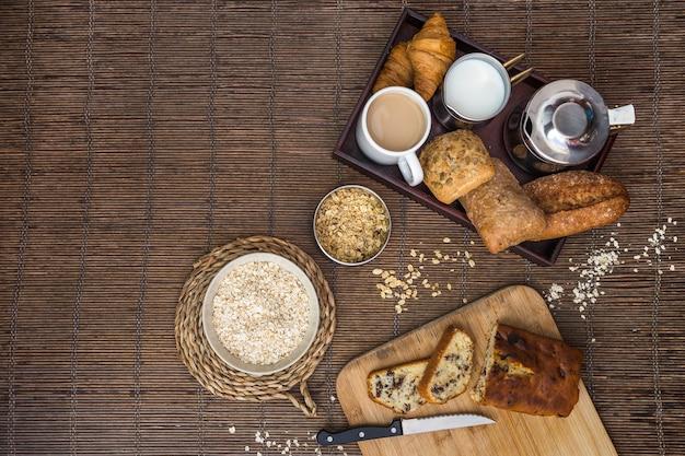 Vue élevée de la nourriture cuite, du thé, du lait et de l'avoine sur le napperon Photo gratuit