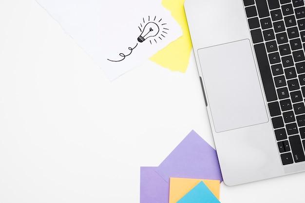 Vue élevée, de, ordinateur portable, et, papier kraft coloré, sur, bureau blanc Photo gratuit