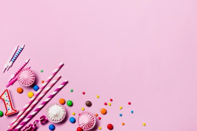 Une vue élevée de pailles à boire; bougies; des gemmes; banderoles et pépites au coin du fond rose Photo gratuit
