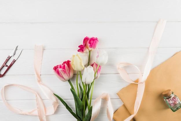 Vue élevée de papier brun; fleurs de tulipes; ruban et coupe contre le bureau blanc Photo gratuit
