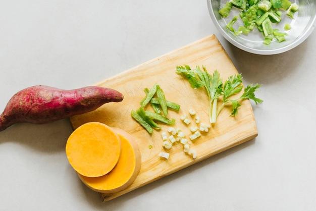 Vue élevée de patate douce; tranches de citrouille et de céleri sur une planche à découper Photo gratuit