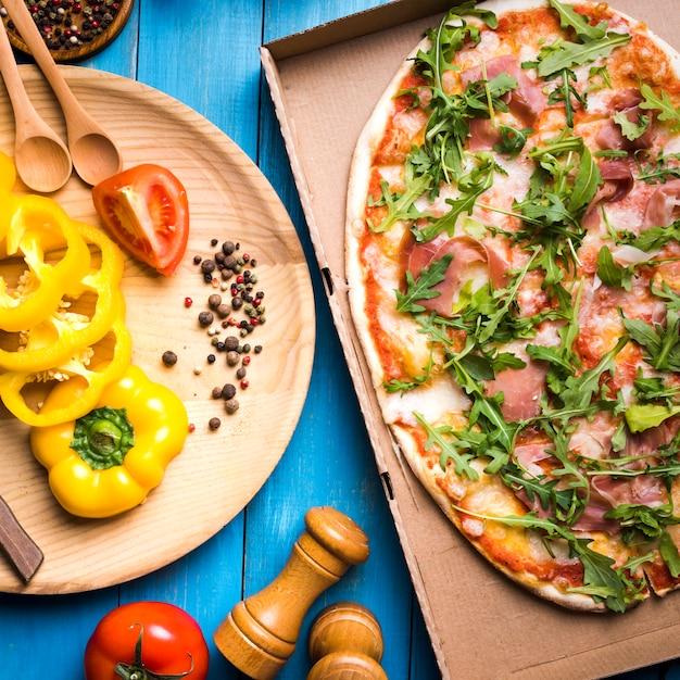Vue élevée de pizza au pepperoni dans une boîte en carton avec des épices; moulin à poivre et légumes sur une table en bois bleue Photo gratuit