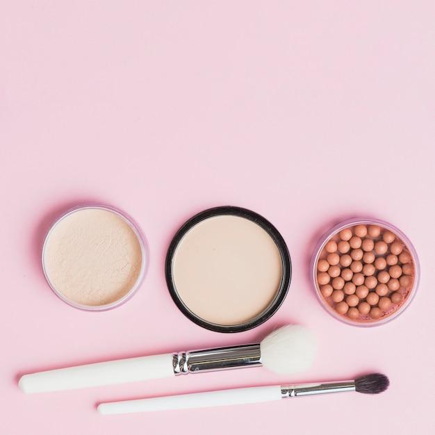 Vue élevée de poudres pour le visage; perles de bronzage et pinceaux de maquillage sur fond rose Photo gratuit