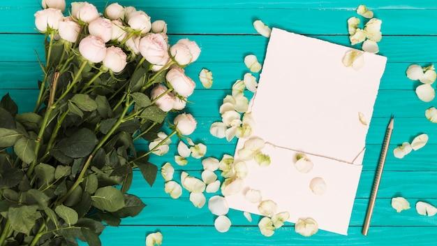 Vue élevée de roses blanches; crayon; papier vierge; et pétales contre une table en bois verte Photo gratuit