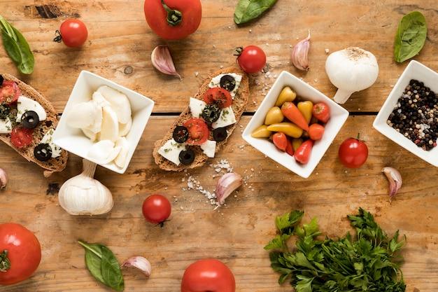 Vue élevée de savoureuse bruschetta et des ingrédients italiens frais sur la table Photo gratuit