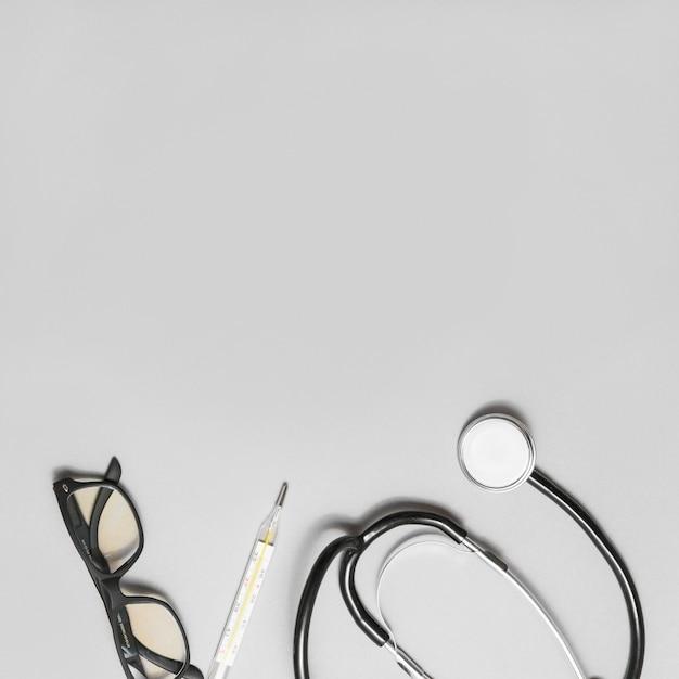 Vue élevée des spectacles; stéthoscope et thermomètre sur fond gris Photo gratuit