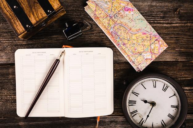 Vue élevée de stylo, agenda, carte et horloge sur fond en bois Photo gratuit