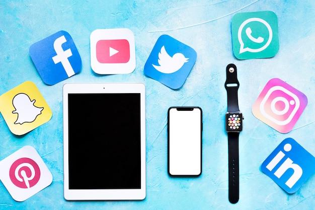 Vue élevée de la tablette numérique, téléphone mobile et montre intelligente avec découpes des icônes d'application Photo gratuit