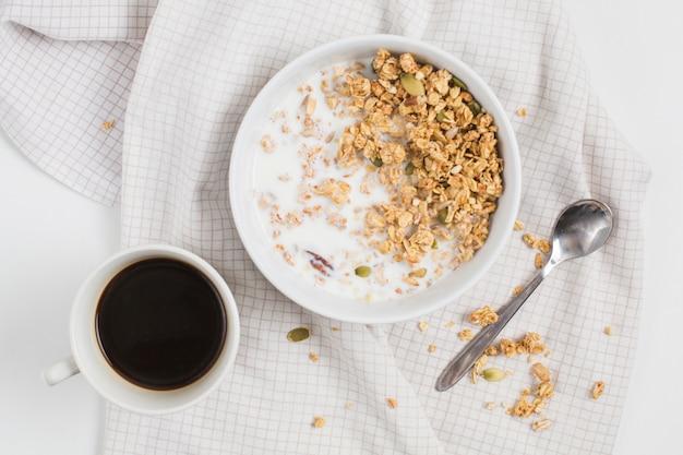 Une vue élevée de la tasse de thé; cuillère et bol d'avoine avec des graines de citrouille sur une nappe Photo gratuit