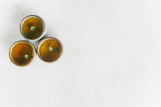 Une vue élevée de tasses à thé à base de plantes sur fond blanc Photo gratuit