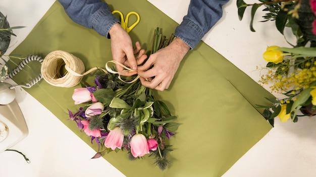 Une vue élevée d'un touriste attachant le bouquet de fleurs avec de la ficelle sur du papier vert sur le bureau Photo gratuit