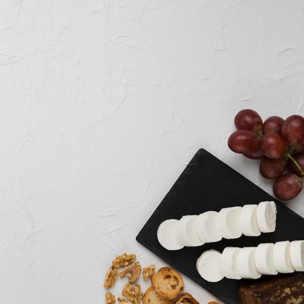 Vue élevée d'une tranche de fromage de chèvre sur une ardoise avec des raisins; pain et noix sur fond texturé Photo gratuit
