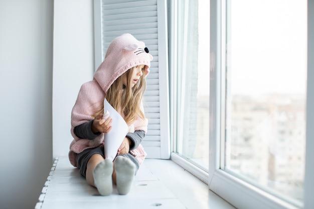 Vue de face adorable petite fille à la recherche sur la fenêtre Photo gratuit