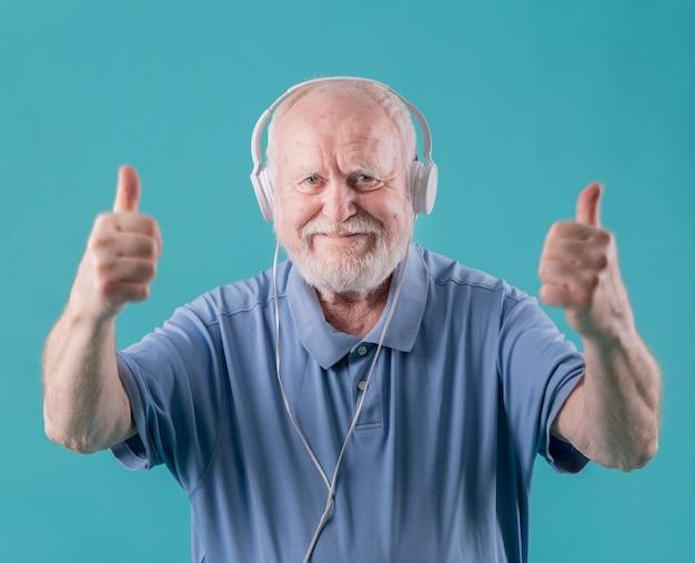 Vue de face aîné avec des écouteurs montrant signe ok Photo gratuit
