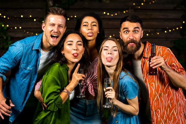Vue de face des amis heureux montrant des langues Photo gratuit